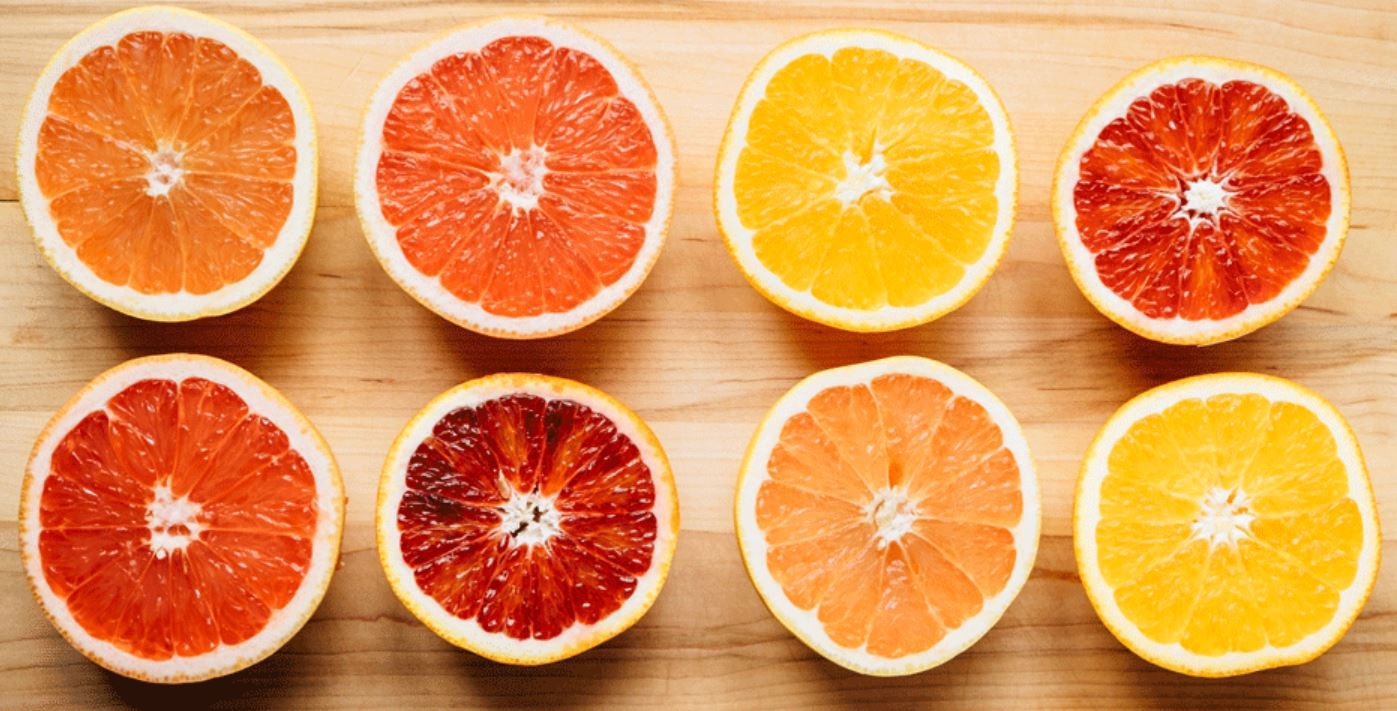 picture of eight open sliced citrus fruits on a wood background. Two rows of four, each with varying colors of orange, yellow, and red