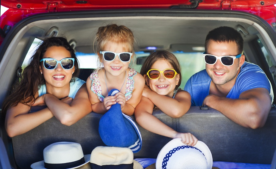 A family is looking out the trunk of their car. They are all wearing sunglasses and they all have hats in the trunk. There is a man on the right, a woman on the left, and two young girls in the center.