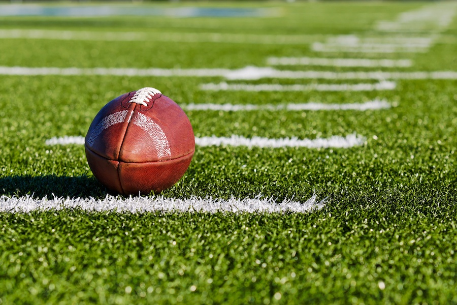 A football on the field between two white lines