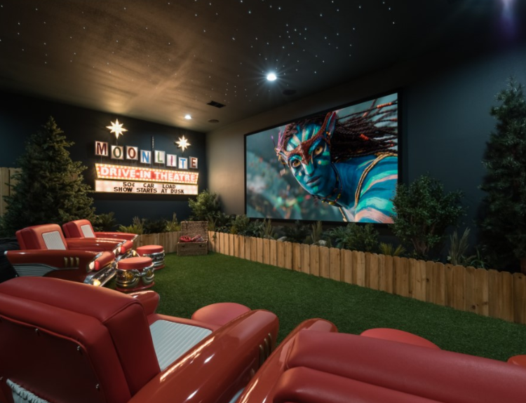 "A small indoor movie theater with large red chairs and turf on the ground with wood railing around and trees around the edge. There is a screen playing the movie Avatar and on the left wall is a sign that says ""Moonlite Drive-In Theatre"""