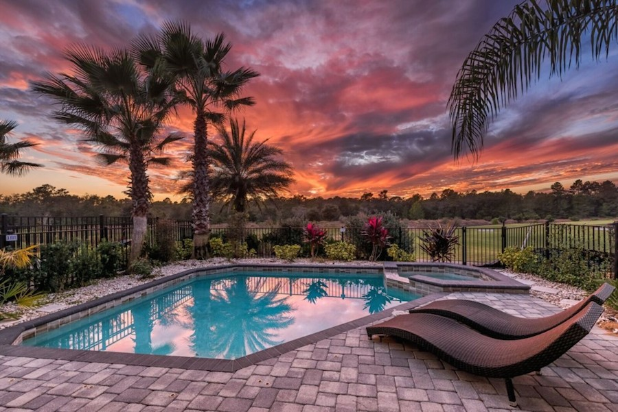 A small pool with attached hot tub with two brown chaises and brick patio. There is a black gate around the pool and palm trees and bushes and pink flowers. There is a beautiful sunset in the back.