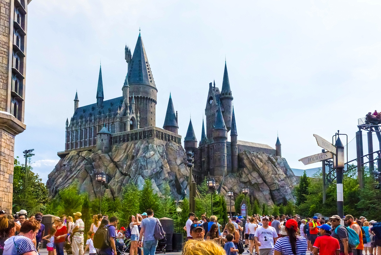 The crowded park with a sign pointing to Hogwarts where you can see a large gray castle on top of a rock structure with blue roofs