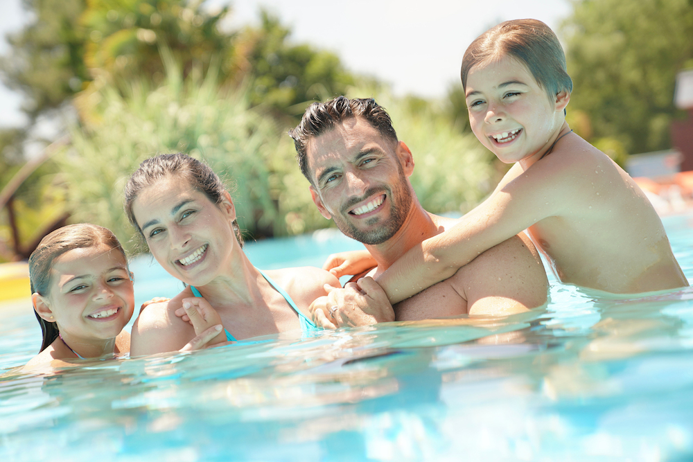 A family swimming in a pool: a little girl to the far left touching her mother, and then a little boy to the far right with his arms around his dad
