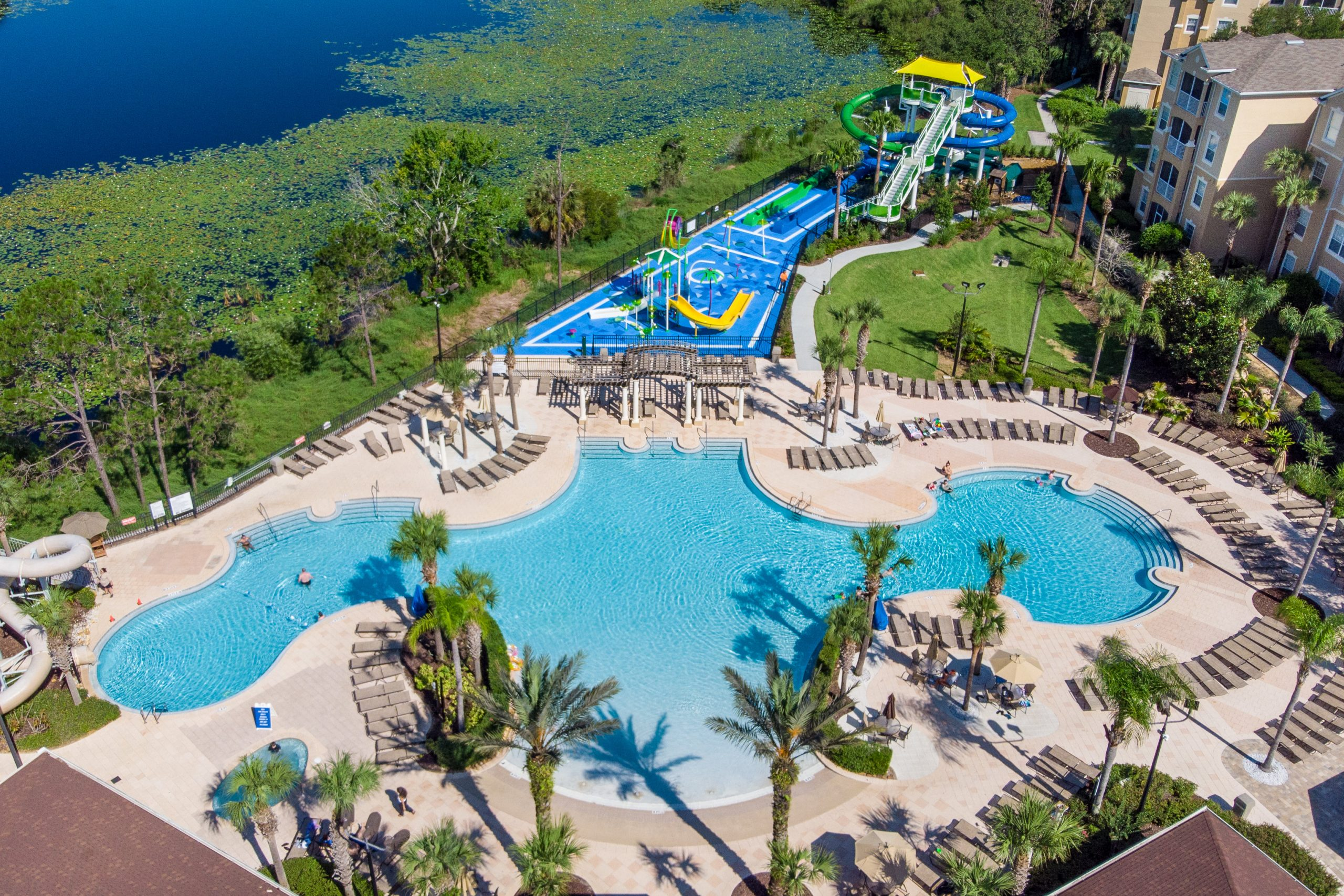 A birdseye view of a giant pool and waterpark next to the water to the right and the resort buildings to the left