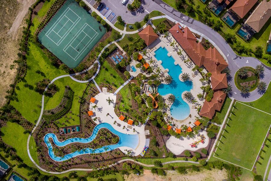 A birdseye view of a resort with two big pools and space in between them, tennis courts behind, and buildings to the right with a long driveway behind and