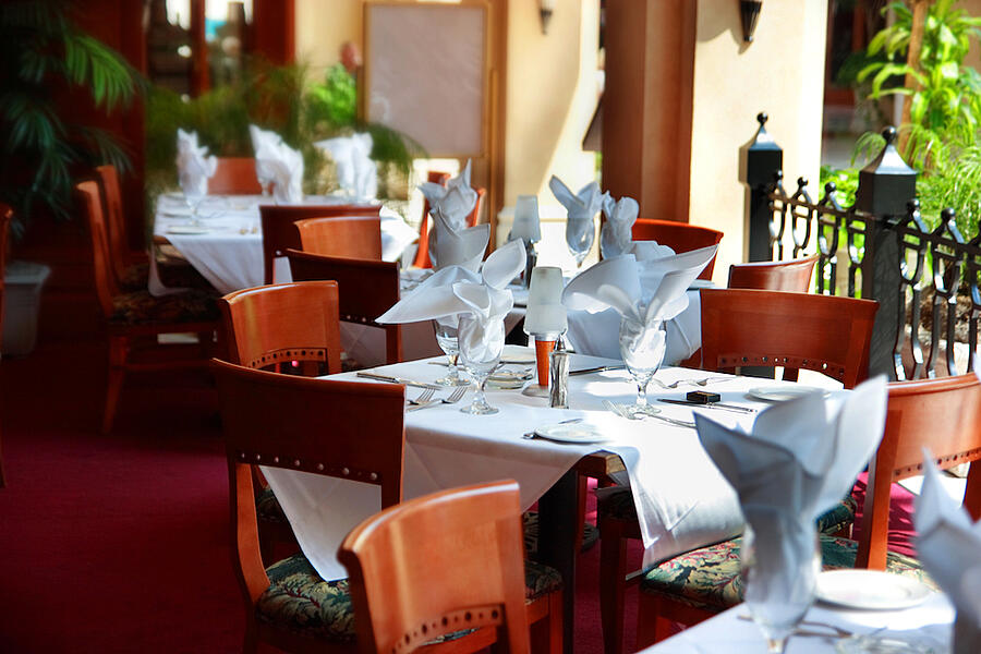 A picture inside of a fancy restaurant that is inside with outdoor space. Tables have four brown chairs and napkins folded into the drinking glasses and white table cloths. There is a red carpet