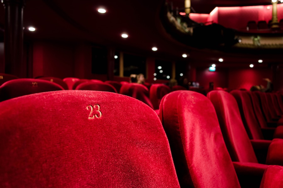 A close up image of red velvet seats in a theater