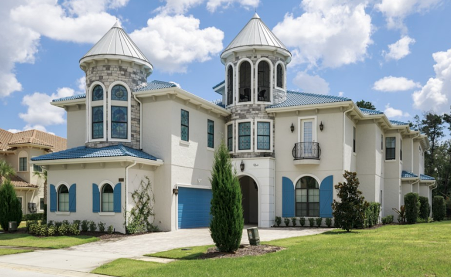 A large mansion that is white with blue details and two large brick columns with stained glass windows above. There is a driveway and a grass lawn with green bushes around.