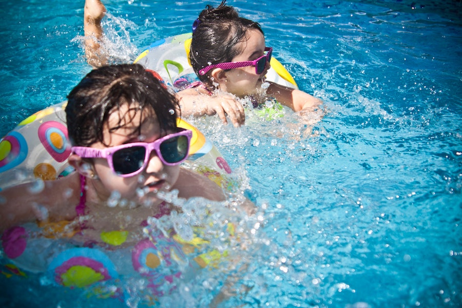 Two little kids wearing sunglasses in floaties in a pool
