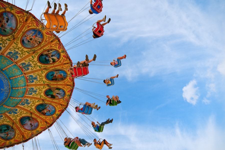 A picture facing up of a bunch of people on a ride that is swings hanging from chains and spinning around in the air