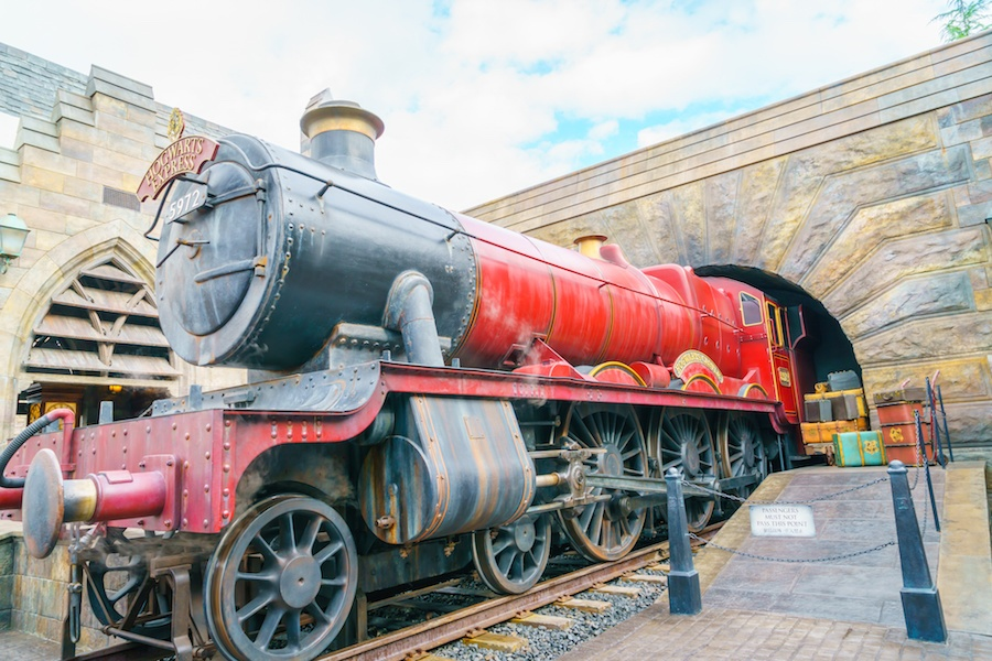 A picture of the Hogwarts Express coming out of a stone tunnel