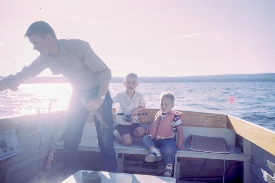 A man and two sons are sitting on a boat in the water and they are fishing