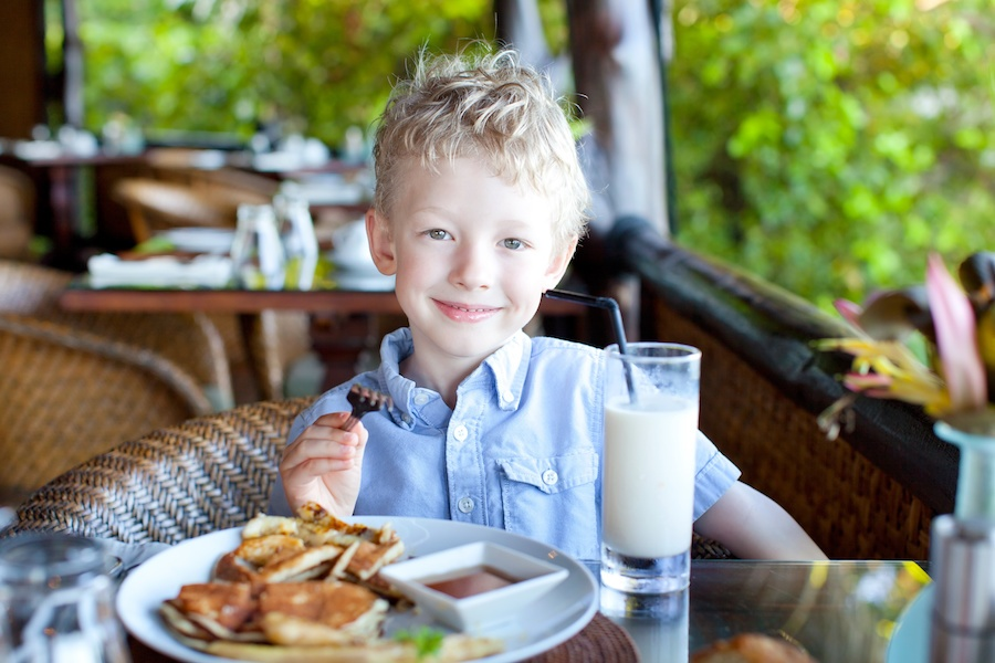 A little boy is eating a meal and drinking a milkshake at a restaurant and smiling.