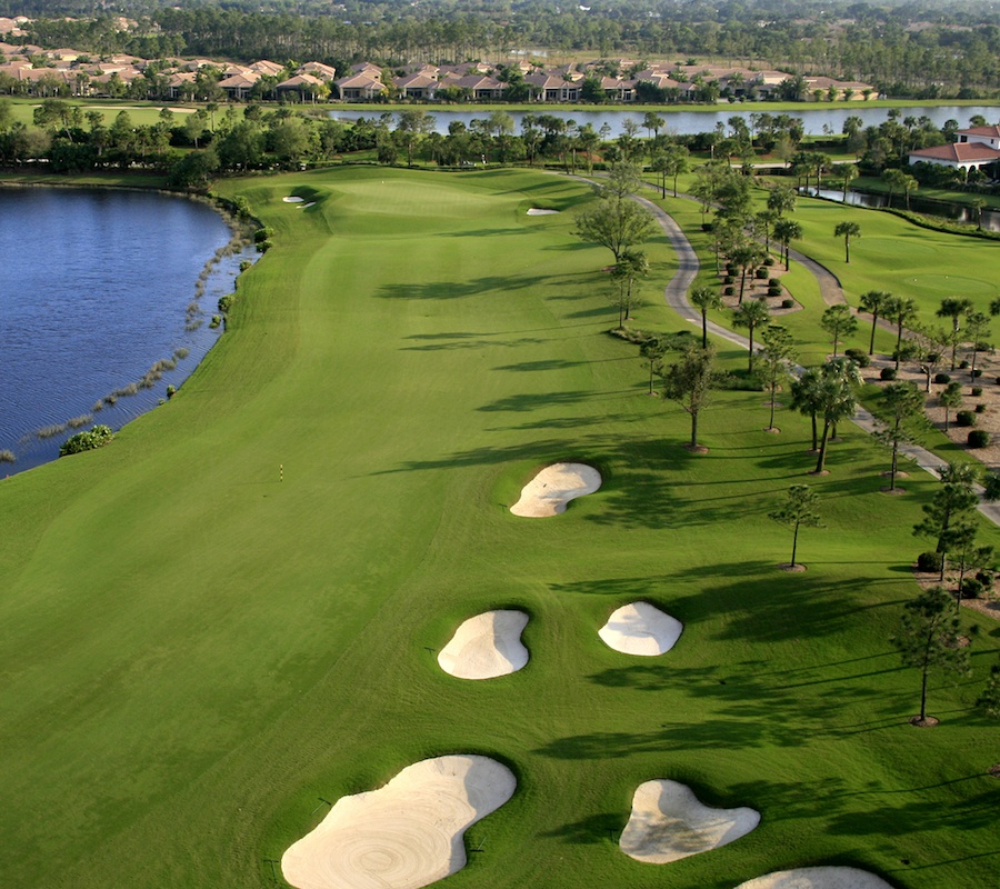 Birdseye view of the golf course with sand pits and water to the left, palm trees to the right, and houses in the background