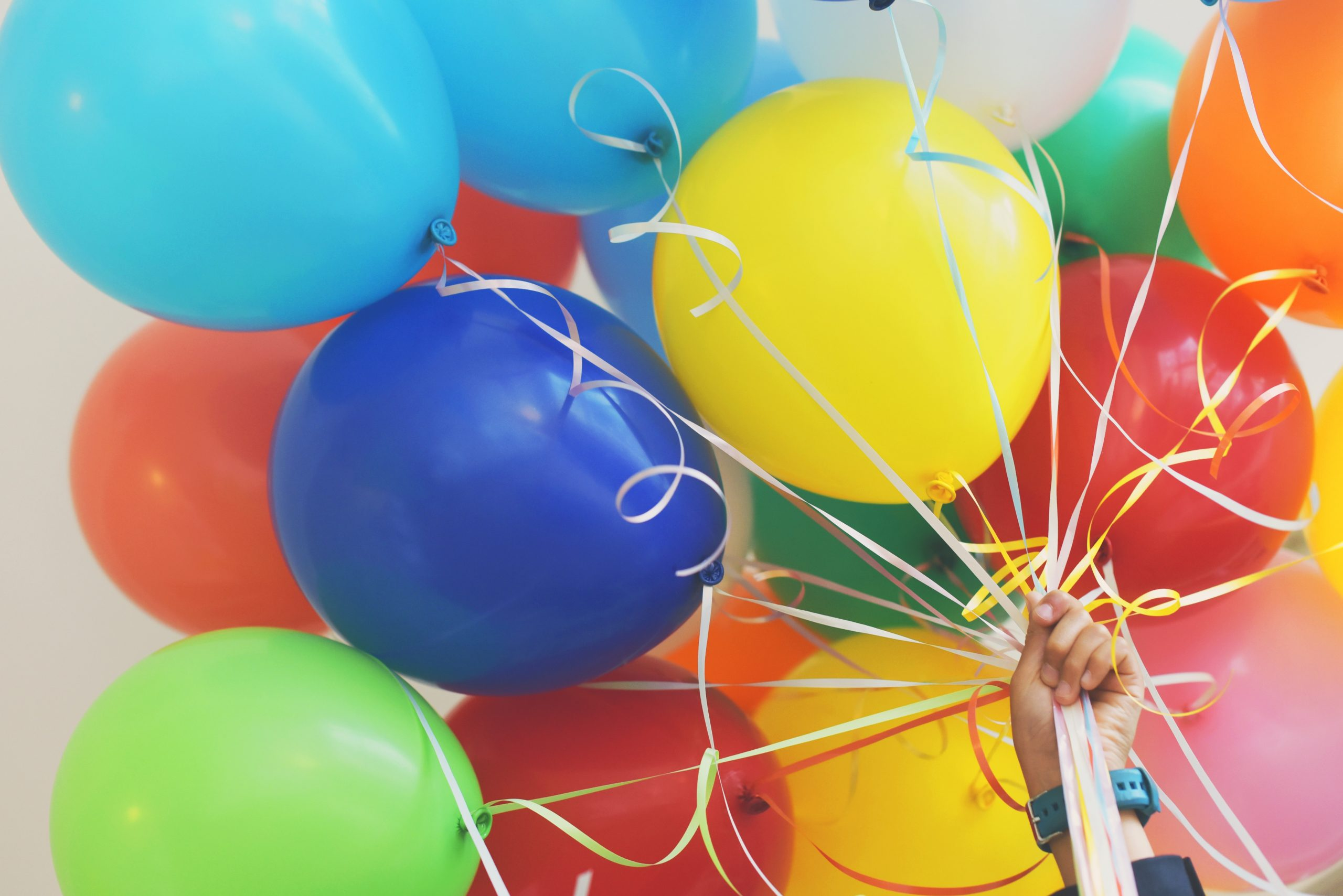 Close up of colorful balloons being held by a hand