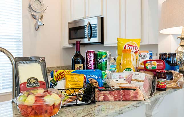 Countertop with lots of food: chips ahoy, bacon, bud light, lays chips, corn flakes, frosted flakes, bread, strawberry jam, butter, eggs, orange juice, sprite, cherry coca cola, a bottle of wine and two bottles of water