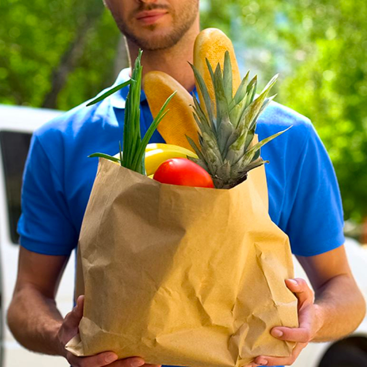 A man holding a paper bag filled with groceries