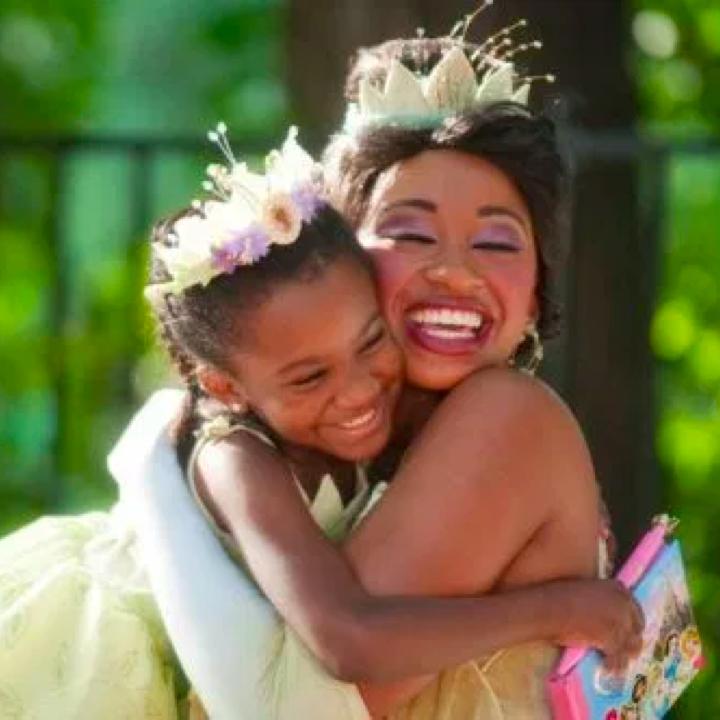 A young girl dressed as Princess Tiana is hugging Princess Tiana