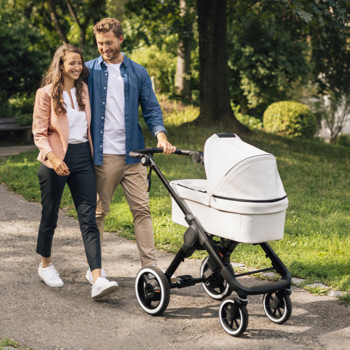 A man and a woman are walking through a park and pushing a baby stroller