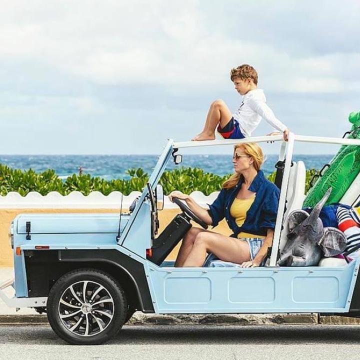 A woman is driving a blue open sided car alongside the beach. A little boy is sitting on top