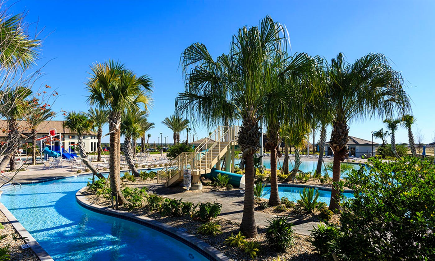 Winding pool surrounded by palm trees and waterslides at ChampionsGate Resort