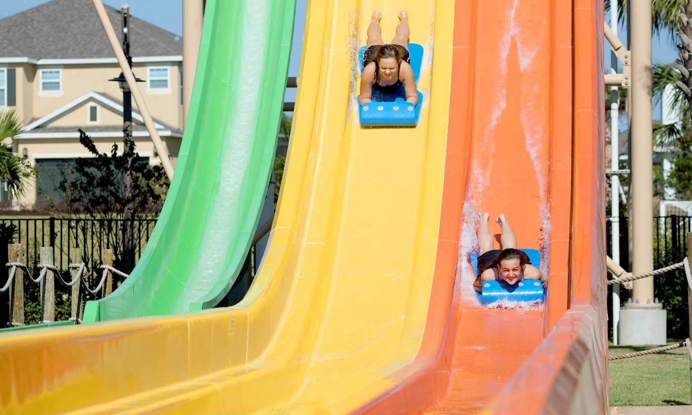 Two people racing down a watersllide