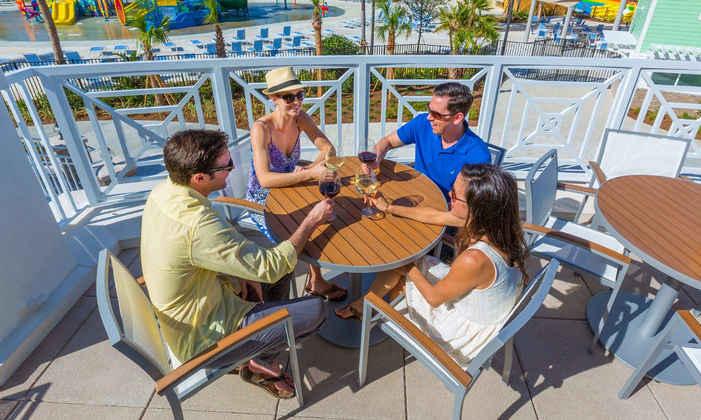 Group of four adults sharing a drink outdoors