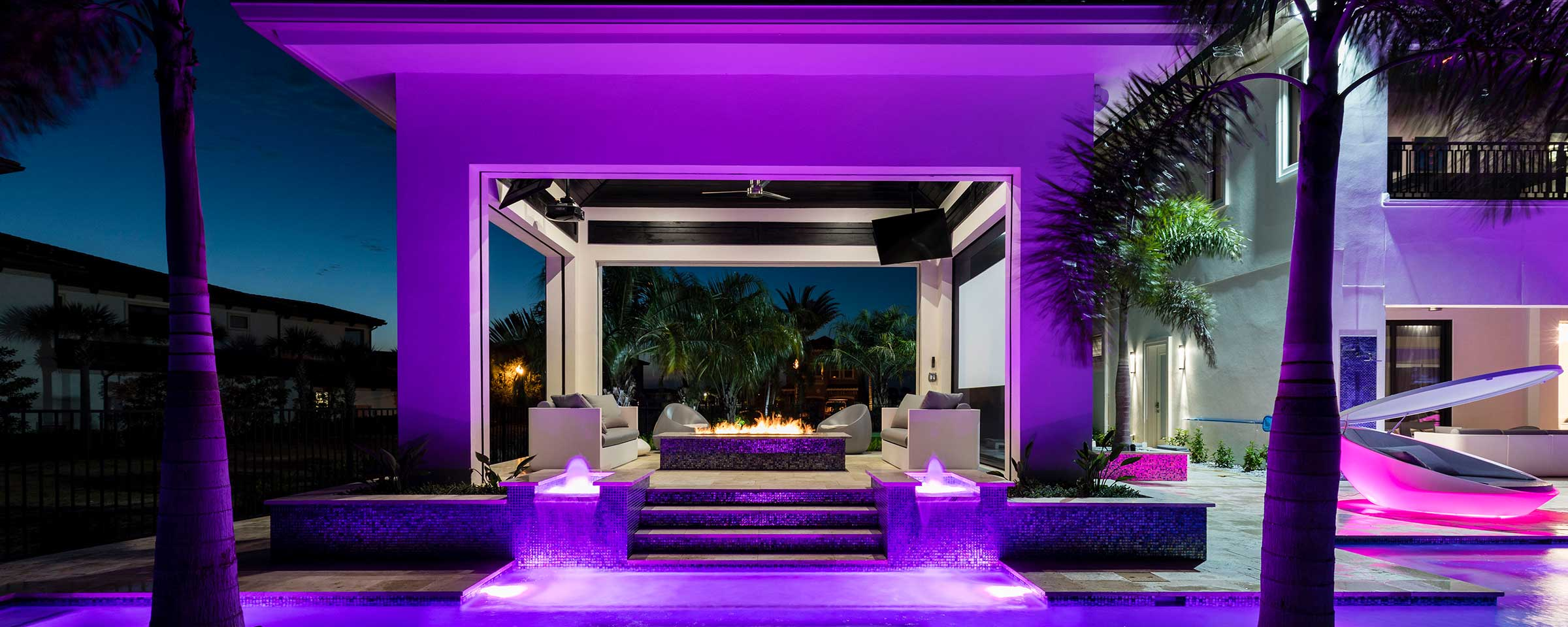 Purple pool lights on in the evening surrounding cabana with wood burning fire in the center.
